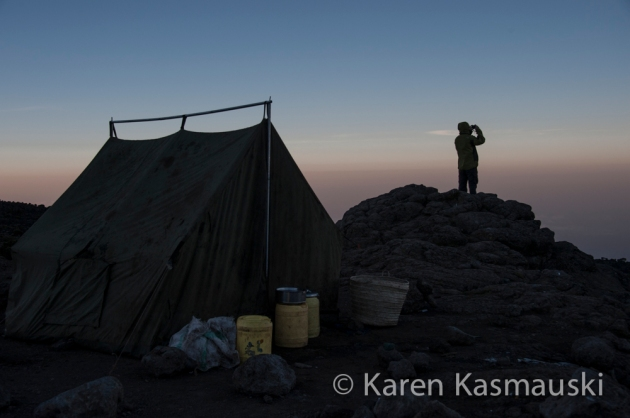 A trekker looks off Kilimanjaro at sunrise.