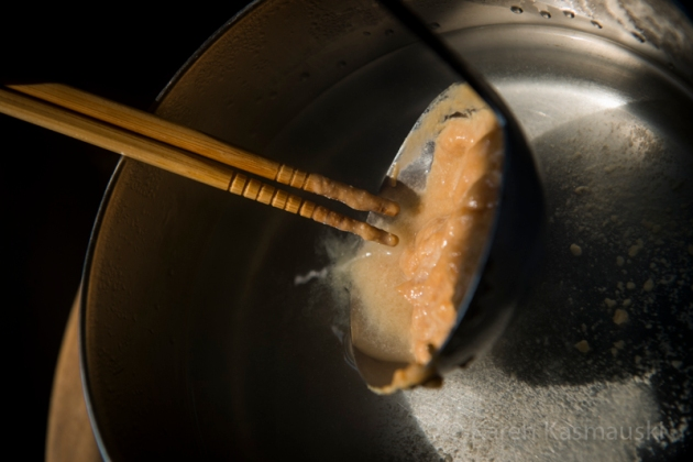 Stirring miso paste into the soup.