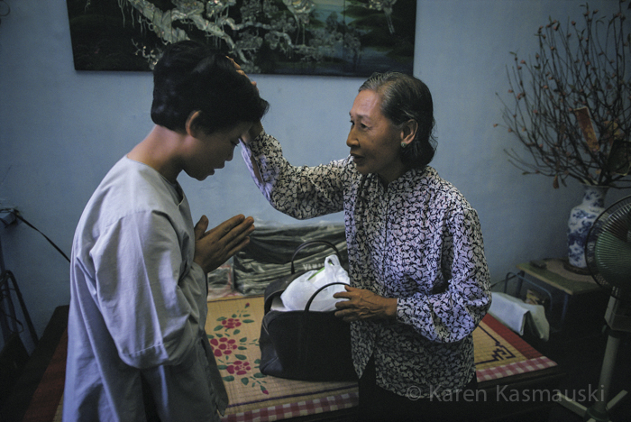 IIn Ho Chi Minh City, Vietnam, a young woman gets a blessing from her aunt before she enters service as a Buddhist nun.