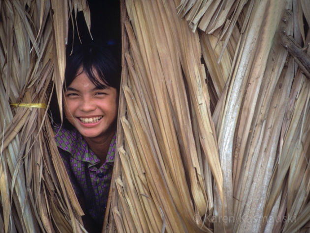 Ho Chi Minh, Vietnam a young girl peers teasingly out at the photographer from behind a pile of reeds