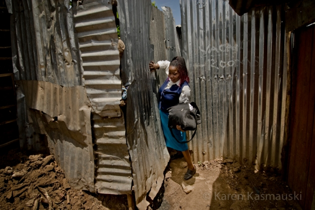 Philomena squeezes through the maze of pathways through the slum to get to her clients.
