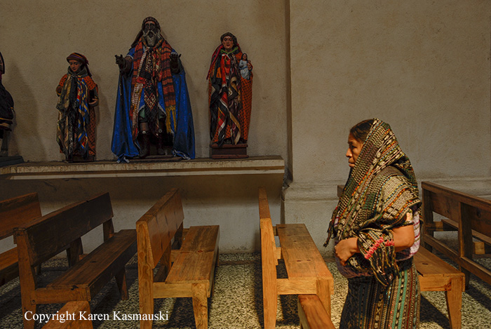 A woman at noon prayer in a Catholic church in Santiago Atitlan Guatemala