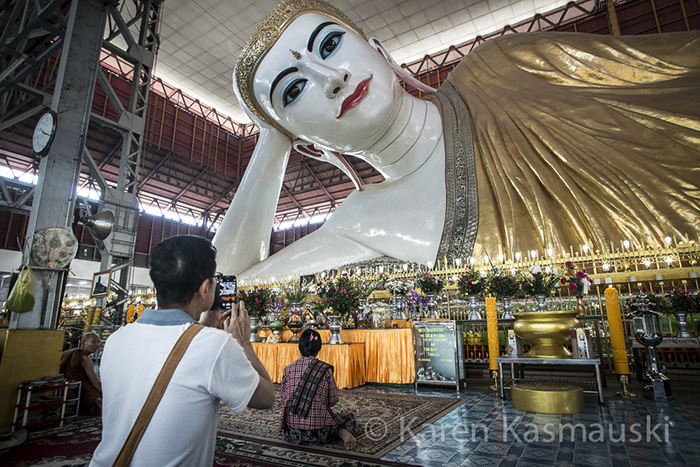 Tourist photographs the famous Reclining Buddha in Yangon, Myanmar.