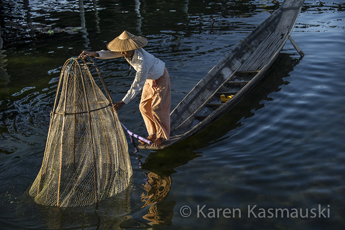 Fisherman collects his net on Myanmar's Inle Lake.
