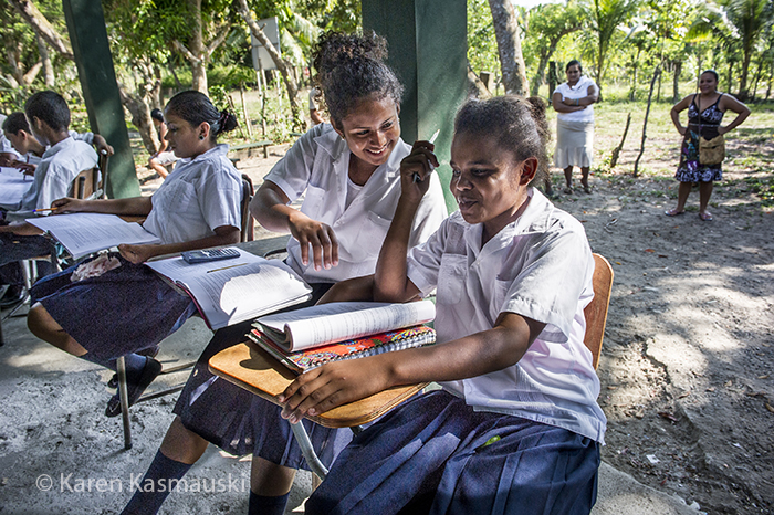 Dunia Hernan, 17, 2nd student from the right, kids her friends during class. She is part of the first ever high school program held in this village. Her father is a fisherman.