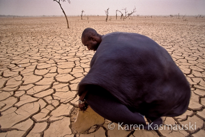 At the height of the dry season in Mali, lakes evaporate.  A village nurse  lifts slabs of mud to look for moisture as the reminants of a sand storm whip across the lake bed.