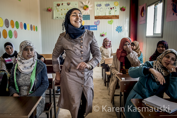 In Jordan at the Azarq temporary school for Syrian refugees, a student rushes up to the blackboard to solve a complex Algebra problem as part of a classroom competition.
